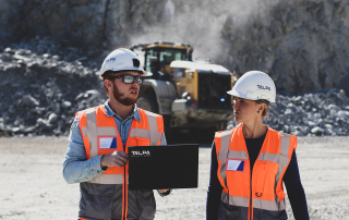talpasolutions employees in front of a heavy machine whose data are processed in the analysis platform
